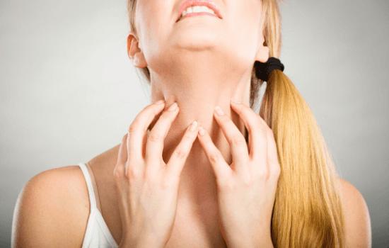 Woman reacting to food allergy symptoms